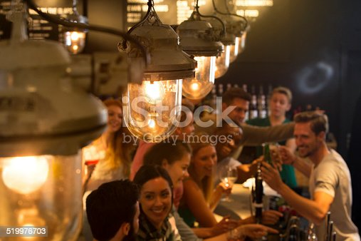 Mixed group of people ordering drinks at the bar