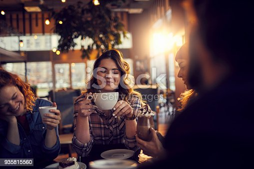 Close up of a group of friends having coffee in a cafe