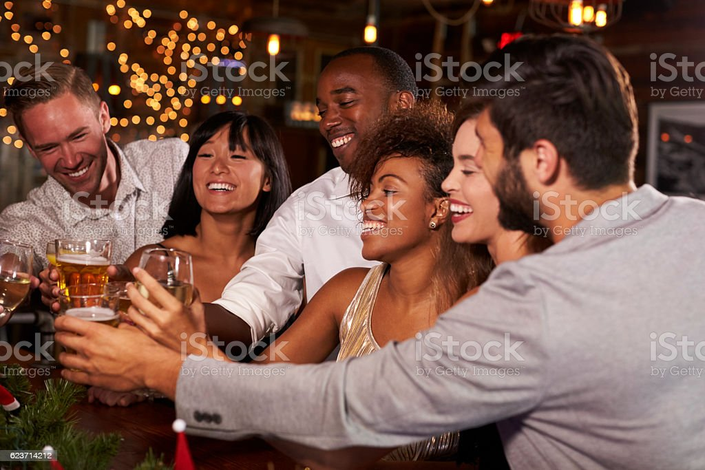 Friends at a Christmas party making a toast at the bar stock photo