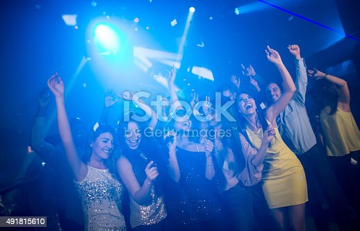 Group of friends having fun at a karaoke party singing and dancing at a nightclub