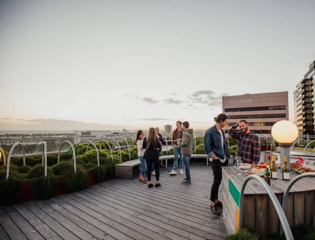 freunde auf einer party auf dem dach - dachgarten stock-fotos und bilder