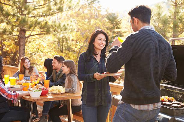 freunde im gespräch bei tisch und zwei barbecue-grill in - paletten terrasse stock-fotos und bilder