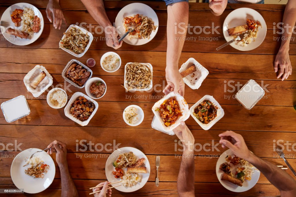 Friends at a table sharing Chinese take-away, overhead view stock photo