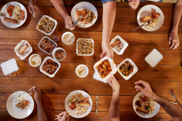 friends at a table sharing chinese take-away, overhead view - chinese food stock photos and pictures
