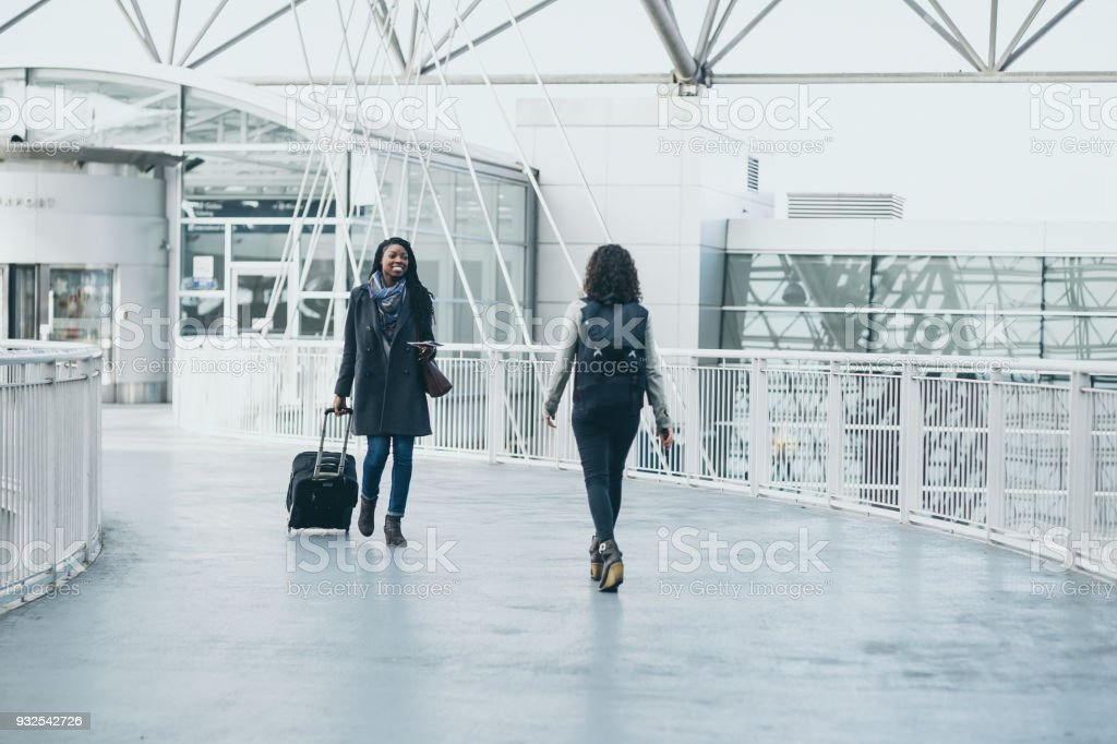 Friends at airport meeting each other stock photo