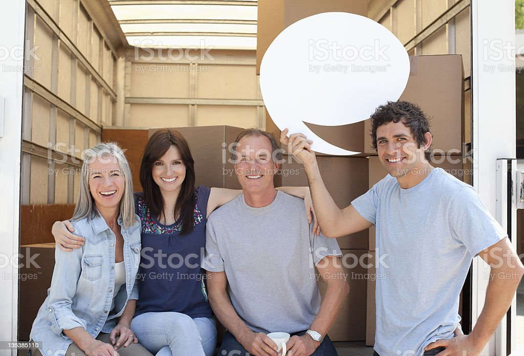 Friends at back of moving van, one holding a comment bubble royalty-free stock photo
