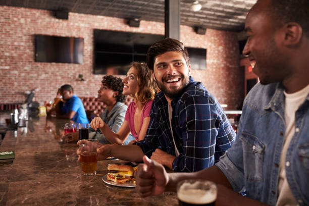 Friends At Counter In Sports Bar Watching Game stock photo