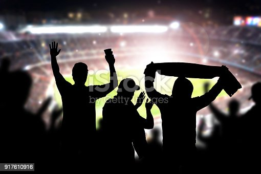 istock Friends at football game in soccer stadium. Crowd cheering and celebrating a goal in arena during match. 917610916