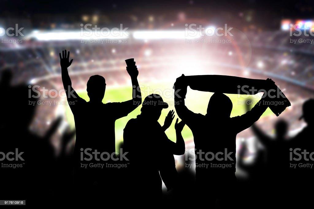 Amigos en el partido de fútbol en estadio de fútbol. La muchedumbre que anima y celebrando un gol en la arena durante el partido. - foto de stock