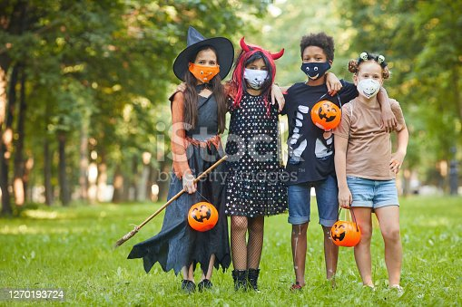 Group of friends in Halloween costumes looking at camera while standing in the park they celebrating Halloween party