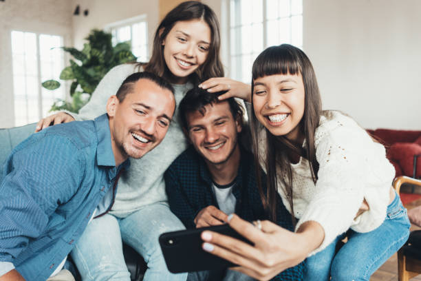 Friends at home party. Four people taking group picture using mobile phone camera stock photo
