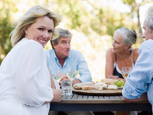 friends at meal outdoors - 60 69 years stock photos and pictures