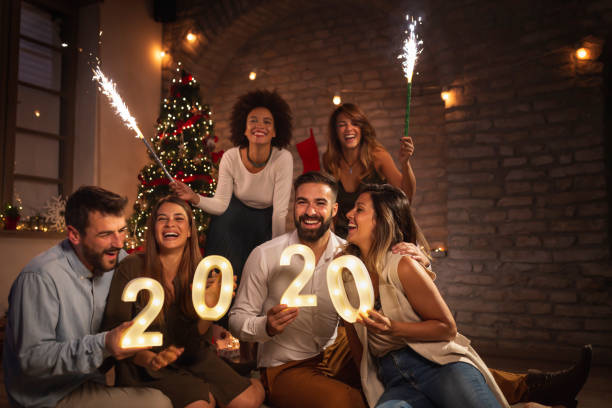 Friends at New Years Eve party Group of young friends having fun at New Years party, holding illuminative numbers 2020 representing the upcoming New Year and waving with sparklers at midnight countdown pyrotechnic effects stock pictures, royalty-free photos & images