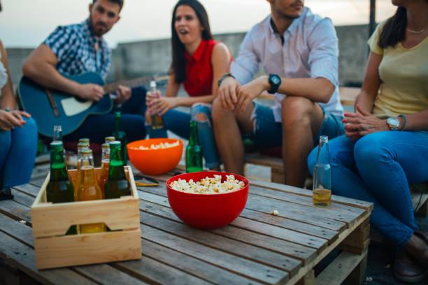 freunde auf party auf dem dach - spielabend snacks stock-fotos und bilder