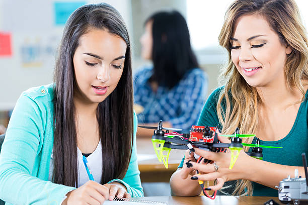 Friends at STEM school work on drone stock photo