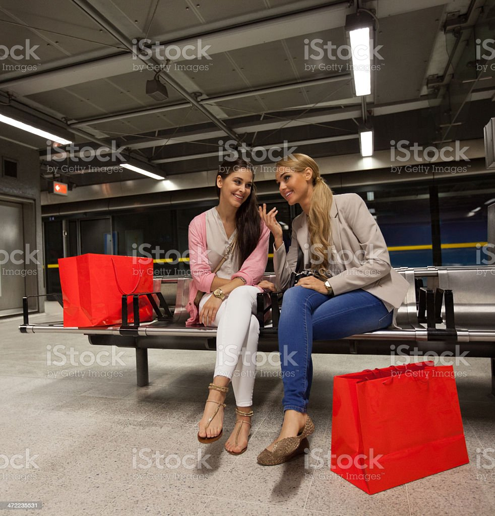 Friends at Subway Station Two young women sitting on a bench at the subway station, waiting for a train. 20-24 Years Stock Photo