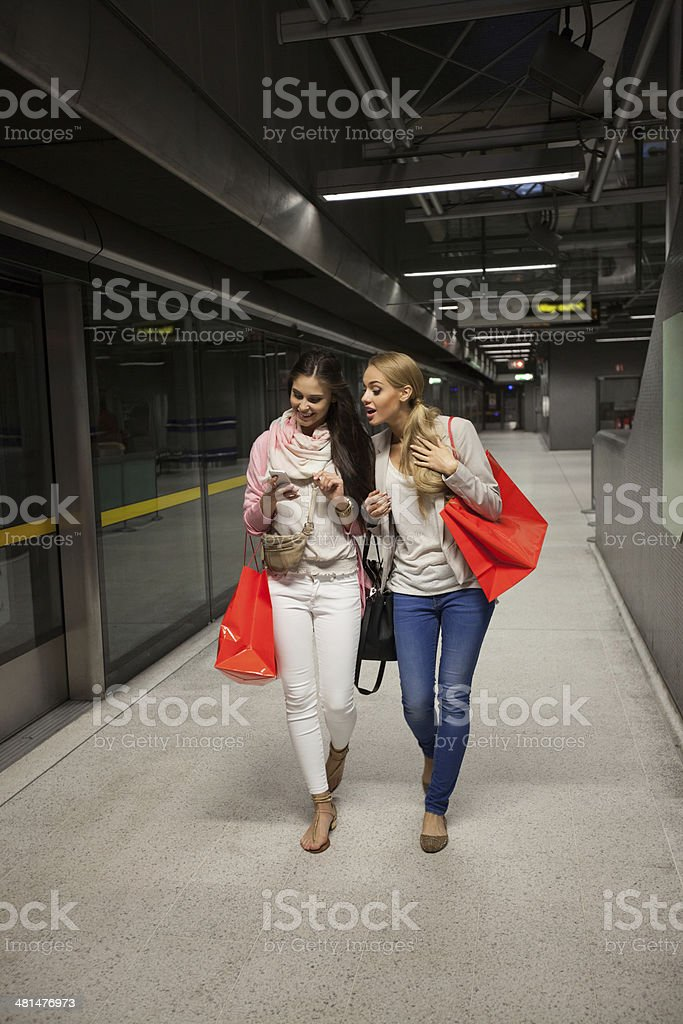 Friends at Subway Station Two young woman walking at the subway station, holding shopping bags and watching at smart phone.  20-24 Years Stock Photo