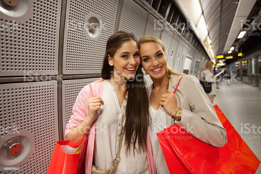 Friends at Subway Station Two young women waiting for a train at subway station, smiling at camera. 20-24 Years Stock Photo
