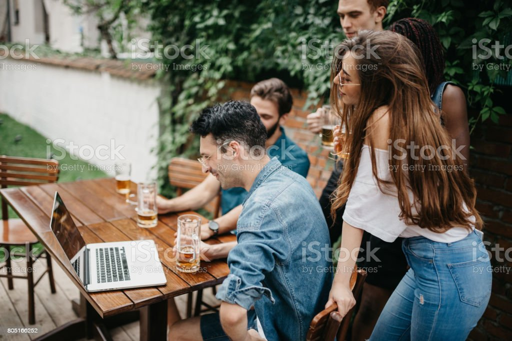 Friends At The Pub Watching Tv Series On The Laptop Stock Photo