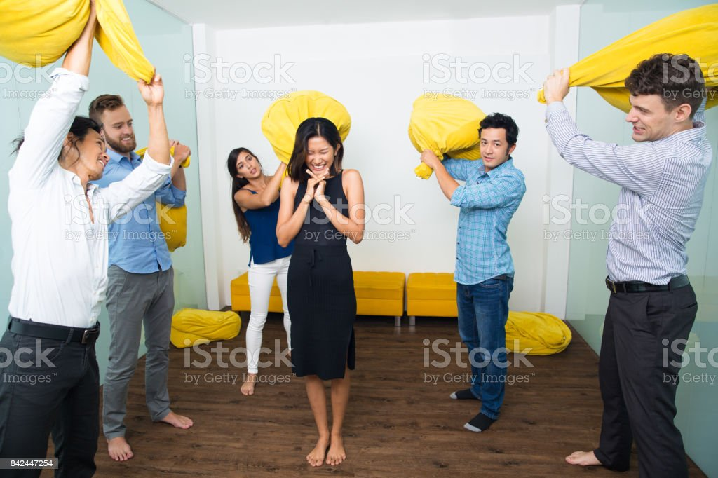 Friends Beating Scared Woman With Pillows стоковое фото