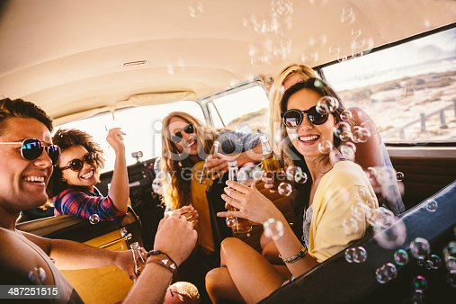 A group of friends inside a van are blowing bubbles and having a good time.  The group is made up of two men and three women.  They are all wearing sunglasses.