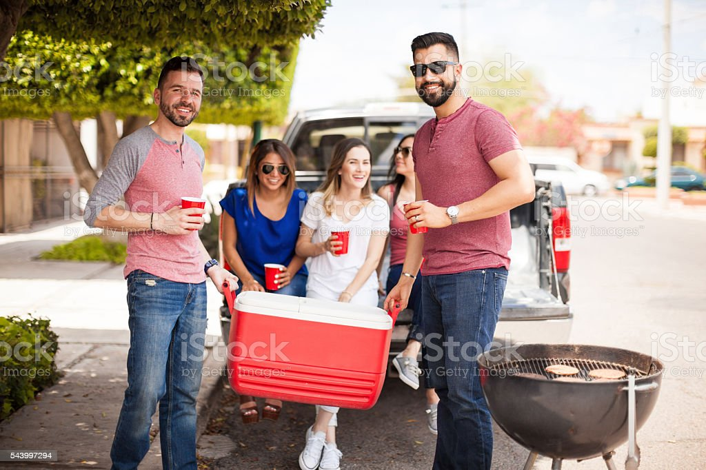Friends bringing drinks to a barbecue stock photo