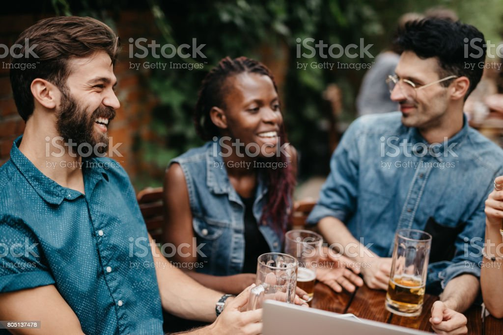 Friends burst in laugh at the pub stock photo