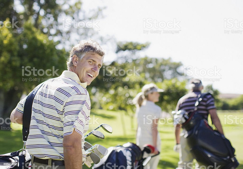 Friends carrying golf bags royalty-free stock photo