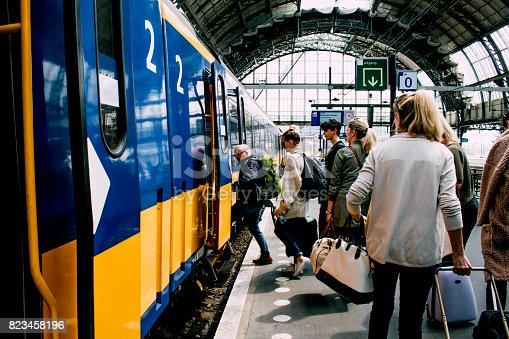 A group of friends getting on the train in Amsterdam.