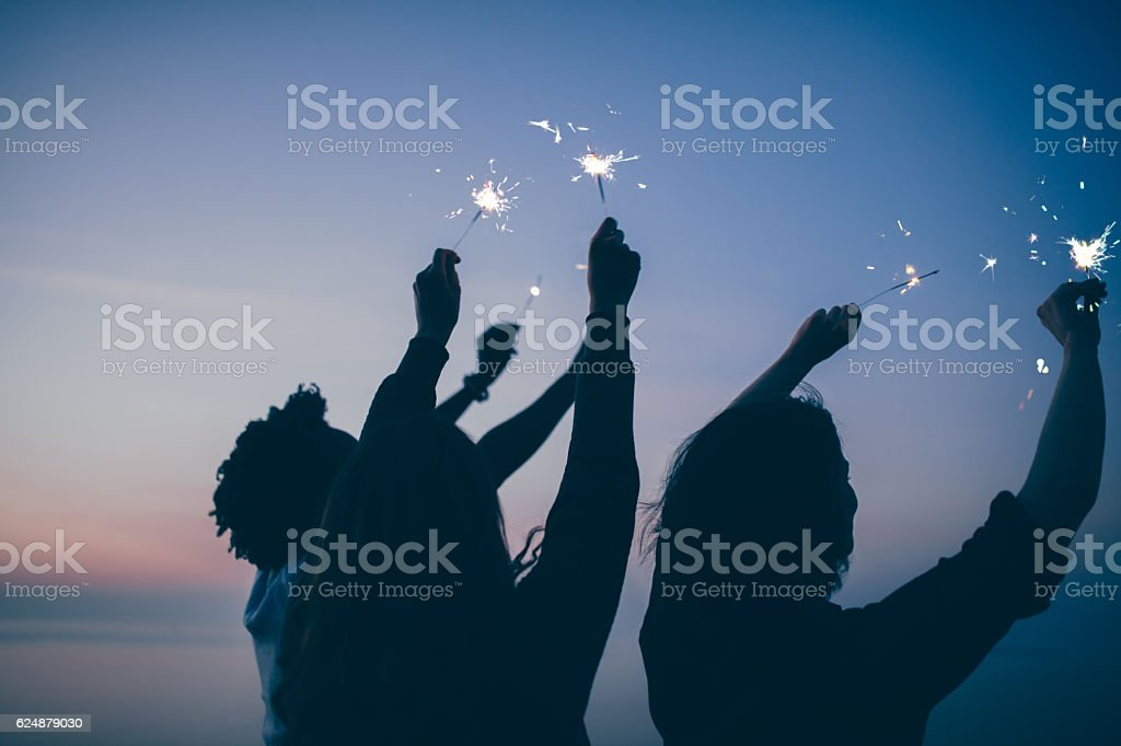Friends celebrate party with sparklers and firework at sunset stock photo