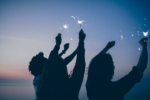 friends celebrate party with sparklers and firework at sunset - independence day stock photos and pictures