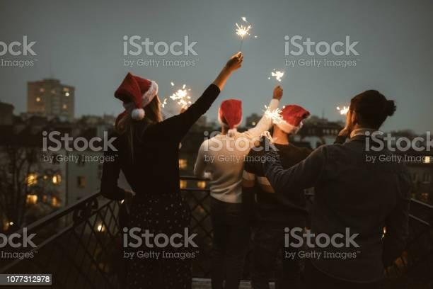 Friends celebrate the christmas on the rooftop picture id1077312978?b=1&k=6&m=1077312978&s=612x612&h=pnjbjhsubestcwxk7ioazbbsziulunv rkcyexojphm=