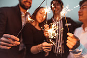 istock friends celebrate the new year on the rooftop 1083832644