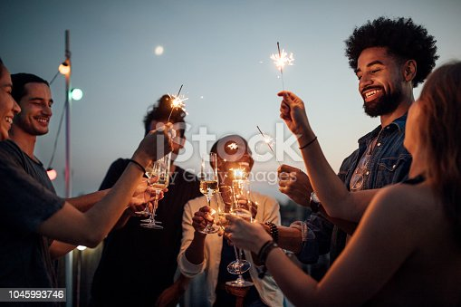 Multiracial young men and women on roof raising wineglasses and sparklers. Friends celebrating at reunion party on rooftop.