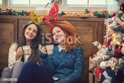 Two friends at a Christmas party sitting on the floor and drinking a eggnog