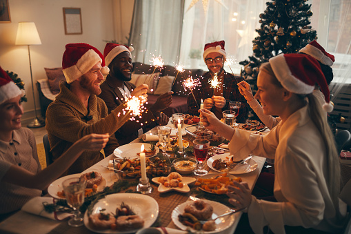 Multi-ethnic group of people holding sparklers while enjoying Christmas dinner at home