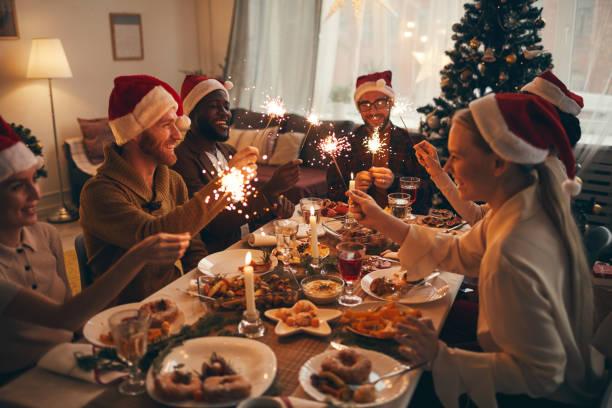 friends celebrating christmas together - cena natale foto e immagini stock