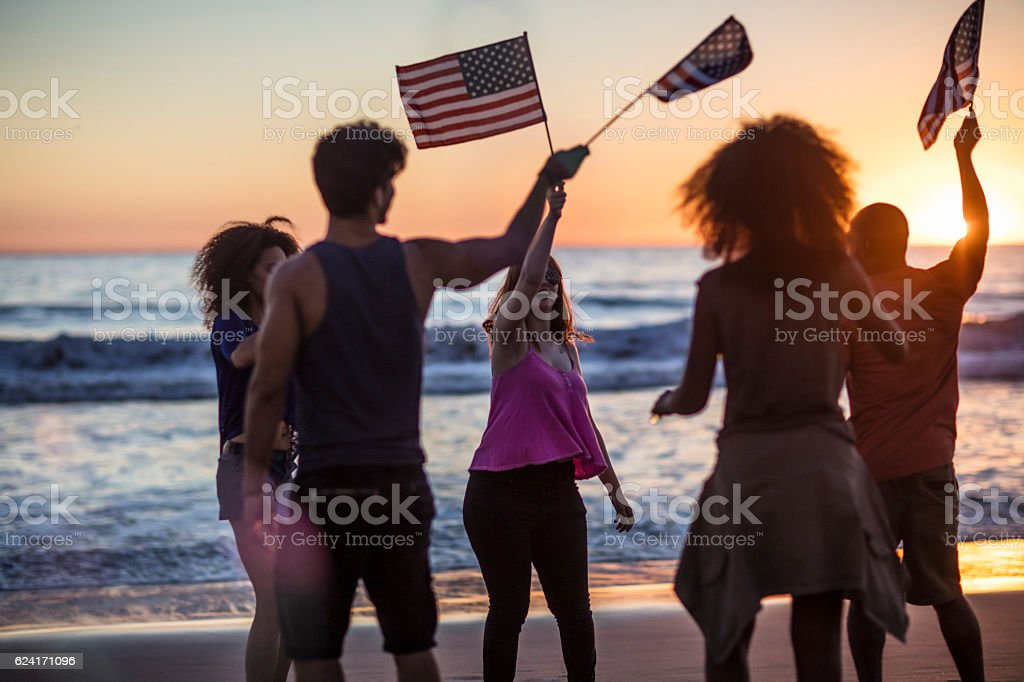 Friends celebrating independence day on the beach stock photo
