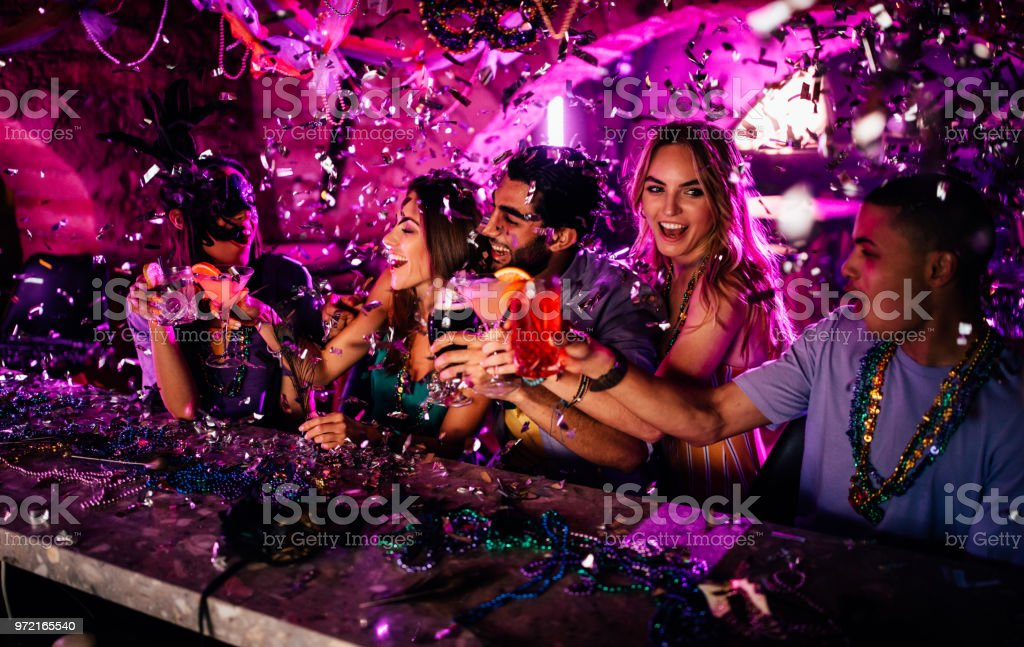 Friends celebrating Mardi Gras with drinks at night club stock photo