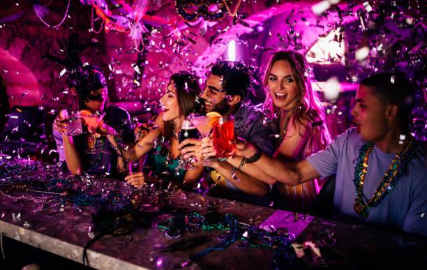amigos comemorando o mardi gras com bebidas no clube noturno - mardi gras - fotografias e filmes do acervo