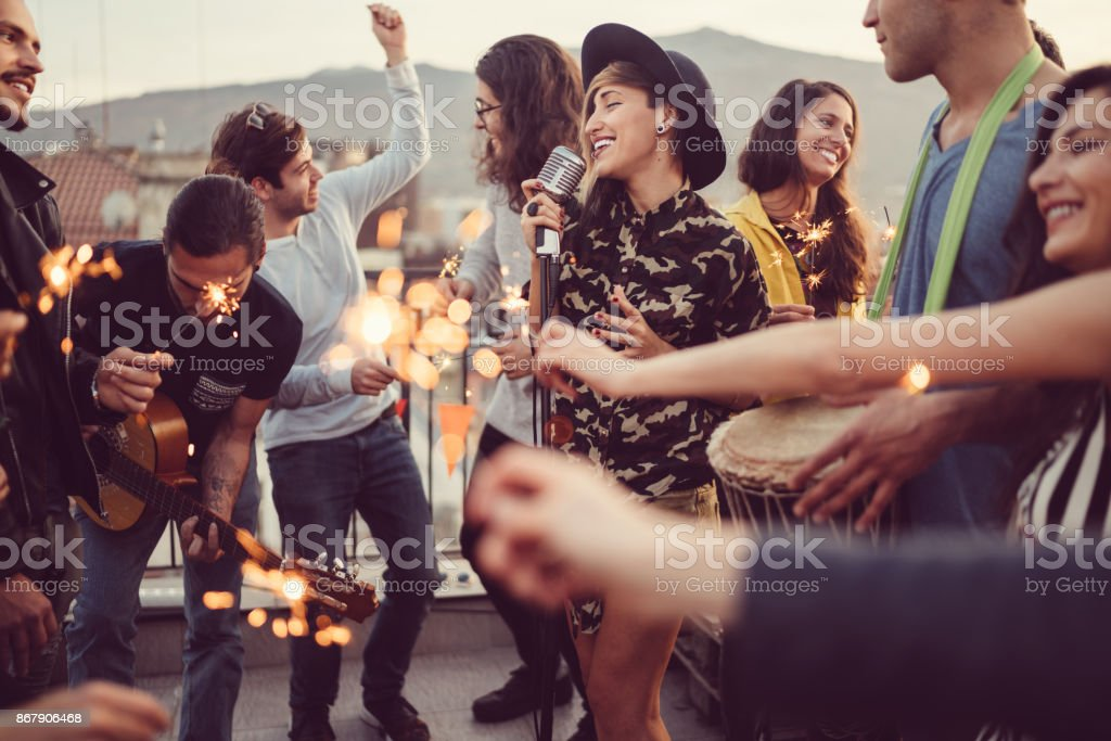 Friends celebrating New Year on rooftop party stock photo