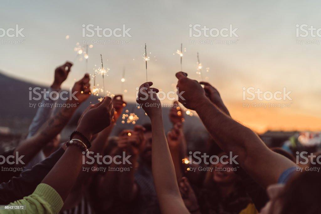 Amigos celebrando año nuevo en la azotea - foto de stock