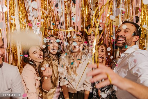 Smiling group of friends celebrating New Year's Eve on a party