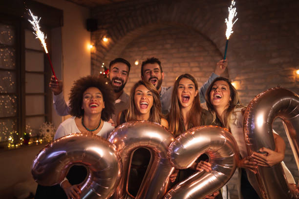 Friends celebrating New Years Eve waving with sparklers and holding 2020 balloons stock photo