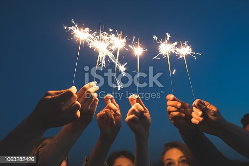 Close up of young people hands holding sparklers against sky. Friends celebrating new years eve with fireworks.