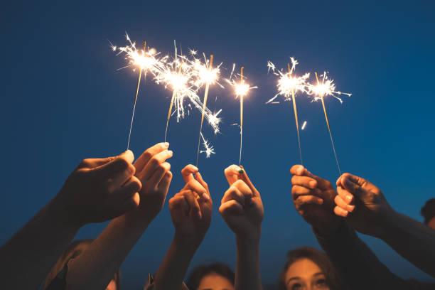 amigos comemorando o ano novo com fogos de artifício - estrelinha - fotografias e filmes do acervo