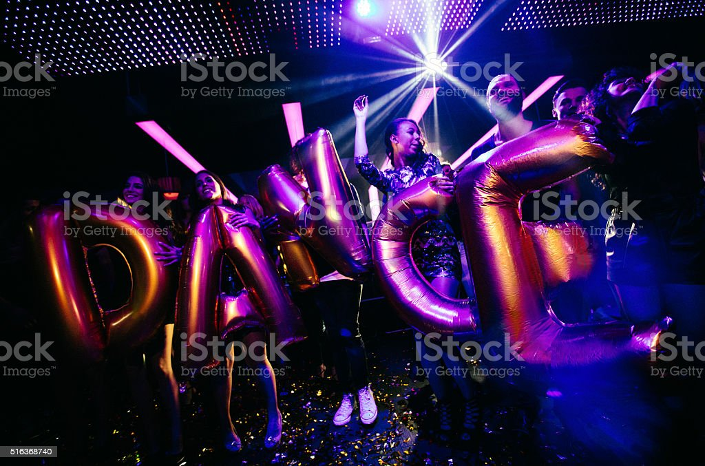 Friends celebrating night club party with confetti and ballons stock photo