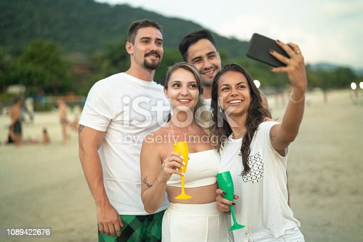 istock Friends Celebrating taking a selfie on Beach Holiday Party 1089422676
