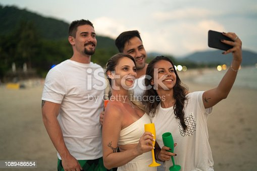 istock Friends Celebrating taking a selfie on Beach Holiday Party 1089486554