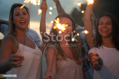 istock Friends celebrating the new year on the beach with sparkler 1089062036